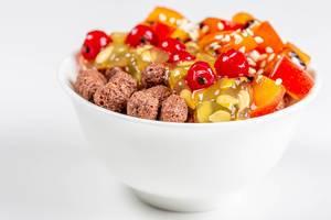 Gesundes Frühstück in weißer Schale mit Maisbällchen, Kiwano Horngurke, Tamarillo und anderen Früchten mit weißem Hintergrund