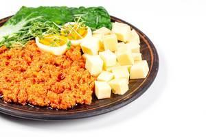 Gesundes Frühstück: Käse, Eier, Gemüse und Zucchinikaviar auf einem Teller vor weißem Hintergrund