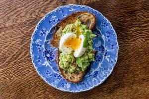 Gesundes Frühstück: Mehrkornbrot-Toast mit Avocado, Ei, Lime, Chili auf einem Retro-Chic Teller, Aufnahme von oben