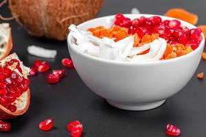 Gesundes Frühstück mit Haferflocken, Kokosnuss, getrockneter Aprikose und Granatapfel-Kernen in einer weißen Schale auf dunklem Hintergrund