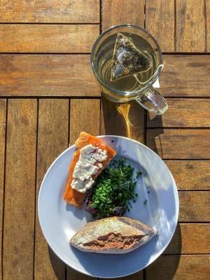Gesundes Mittagessen, mit einem Stück Räucherlachs mit weißer Creme, grünem Salat und ein Brötchen, neben einem Glas Tee mit dreieckigem Teebeutel