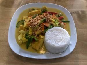Gesundes Mittagessen mit Kurkuma Curry, Gemüse und weißem Reis, angerichtet auf einem weißen Teller