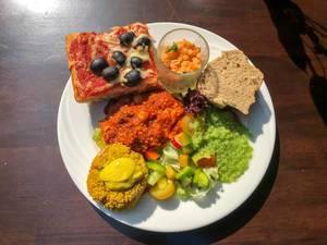Gesundes Mittagessen mit Olivenpizza, Couscous-Curry, Weißbrot und Obstsalat auf einem weißen Teller
