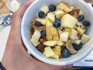 Gesundes Müsli zum Frühstück mit Heidelbeeren, Trockenobst und geschnittener Birne in weißer Schale