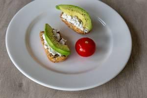 Gesundes, nahrhaftes Frühstück mit Vollkornbrot, Avocado, Hüttenkäse und Tomate