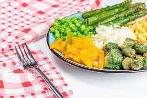 Gesundes Vegetarisches Mittagessen mit verschiedenem Gemüse und Reis auf einem Teller mit Gabel und Küchentuch