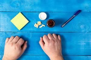 Gesundheitskonzept mit Tabletten auf einem blauen Tisch, neben einem Stift und Notizzettel mit freiem Platz