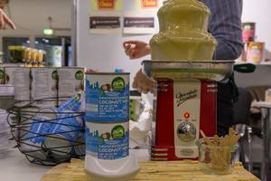 Gesüßte vegane Bio Kokosnuss-Kondensmilch aus der Dose wird in einem Schokoladenbrunnen präsentiert