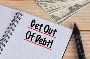 Get out of debt text in notebook and Dollar banknotes on wooden table