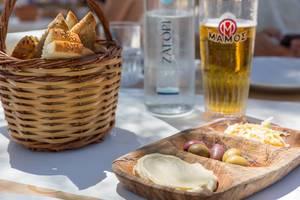 Getränke und ein Brotkorb, neben mediterranem Essen, wie Humus und Oliven, in einem griechischen Restaurant auf Paros