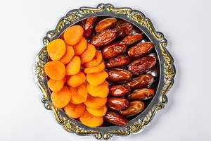 Getrocknete Aprikosen und Datteln dekoriert auf einem runden Tablett vor weißem Hintergrund, aus der Sicht von oben