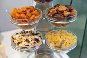 Getrocknete Früchte und Müsli an einem Buffet - Aprikosen, Feigen und kandierte Ananasstückchen in Schälchen