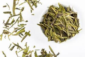 Getrocknete grüne Teeblätter in einer weißen Schüssel und auf weißem Hintergrund verteilt von oben fotografiert