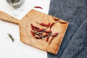 Getrocknete rote Chilis liegen auf Holzbrett, daneben getrocknete Gewürze in Glasdose