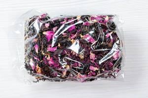 Getrockneter Krim Schwarztee mit rosa Blütenblättern in transparenter Verpackung