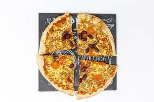 Geviertelte, fleischlose Pizza California mit roten Bohnen und Maiskörnern auf schwarzer Steinplatte