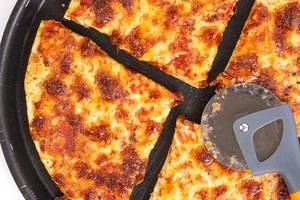 Geviertelte Margherita-Pizza mit einem Pizzaschneider / Pizzaroller