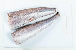 Gewaschener, roher Fisch auf einem Küchenbrettchen