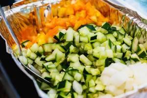 Gewürfelter Salat aus Gurke und Karotte in Aluminiumschale