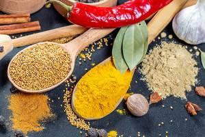 Gewürzarrangement - Currypulver und Senfkörner auf Holzlöffeln mit Lohrbeerblättern, einer roten Chilischote, Zimtstangen, Piment und einer Muskatnuss auf schwarzem Hintergrund
