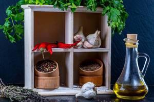 Gewürze und frische Kräuter, wie Petersilie, Chili und Knoblauch in einem Holzregal in hölzernen Gewürzschalen, neben einer Karaffe mit Olivenöl