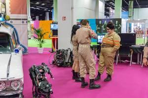 Ghostbusters Darsteller neben Ecto-1 und Proton Pack