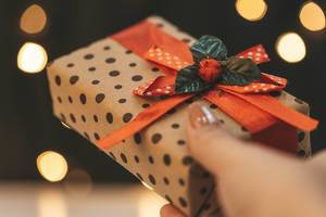 Gift box in hand on bokeh background of glowing garland (Flip 2019)