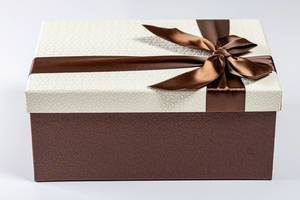 Gift box with brown ribbon and bow on white background (Flip 2019)