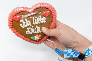 Gingerbread heart from the Oktoberfest with the writing - Ich Liebe Dich - held in hand