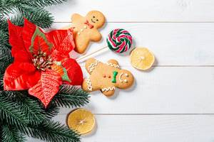 Gingerbread men on stick, a popsicle, and orange slices with christmas tree branches on white background