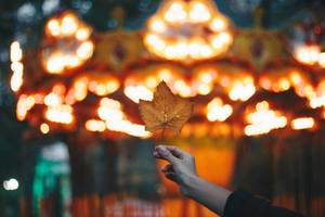 Girl holding a leaf on colorful blurry background. Autumn idea.