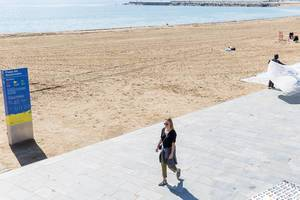 Girl in sunglasses walks at Platja del Somorrostro beach in Barcelona