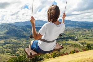 Girl on swing at the clouds in mountain Redonda at Dominican Republic  Flip 2019