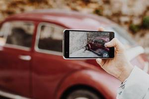 Girl taking photo of retro car with smartphone.