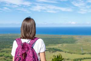 Girl with backpak looks to the ocean from Redonda mountine at Dominican Republic