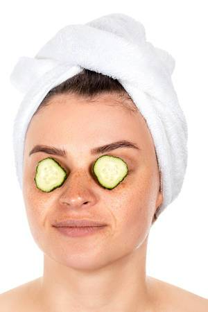 Girl with slices of fresh cucumber on her eyes. The concept of caring for your appearance