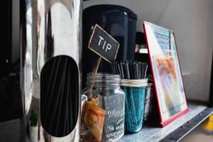 Glas für Trinkgeld neben einem anderen Glas mit Trinkhalmen und ein Bild mit dem Eiskaffeeangebot des Cafes