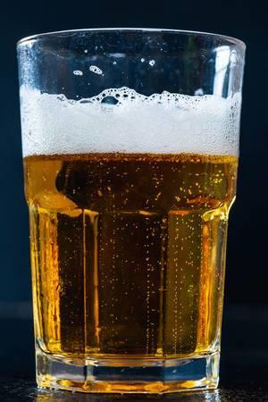 Glas mit Leichtbier und Bierschaum, nicht mehr ganz voll vor dunklem Hintergrund