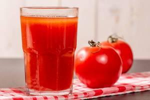 Glas mit natürlichem, frischem Tomatensaft aus ganzen Tomaten