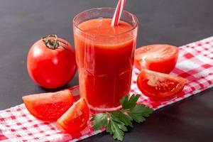 Glas mit organischem Tomatensaft, angerichtet mit ganzer Tomate, Tomatenschnitzen und Petersilie