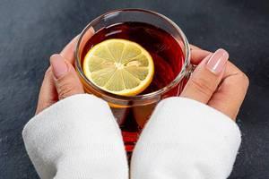 Glas Tee mit Zitrone in den Händen einer Frau in der Nahaufnahme