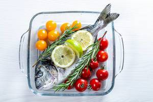 Glass baking sheet with raw Dorado fish and vegetables (Flip 2019)