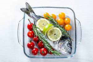Glass baking sheet with raw Dorado fish and vegetables