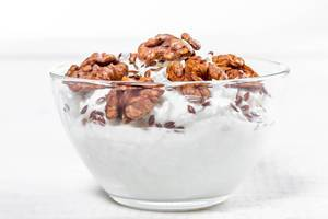 Glass bowl with cottage cheese, nuts and flax seeds on white wooden background (Flip 2019)