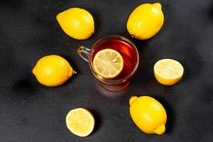 Glass Cup with black tea surrounded by fresh ripe lemons on a black background (Flip 2019)