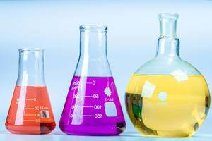 Glass flasks of different shapes with colored solutions. Concept of chemical experiments (Flip 2020)