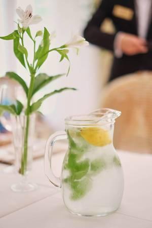 Glass jug of cold lemonade on a light background cafe. Pitcher lemon water with mint. Cold lemonade box  Flip 2019