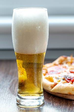 Glass of beer with foam and pizza on the table (Flip 2019) (Flip 2019)