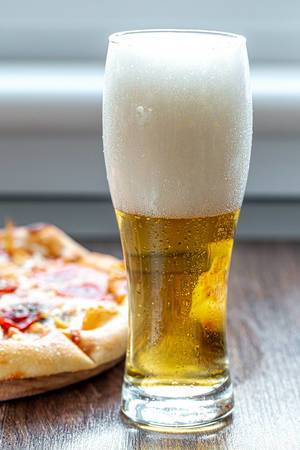 Glass of beer with foam and pizza on the table
