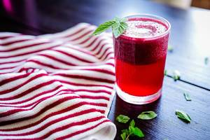 Glass of blackberry smoothie on wooden table